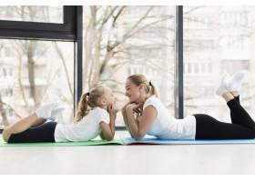母女俩在瑜伽垫上摆姿势侧观_7435866