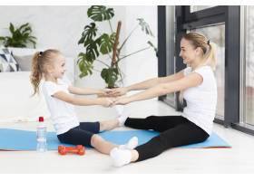 母女俩在瑜伽垫上锻炼的侧观_7435895