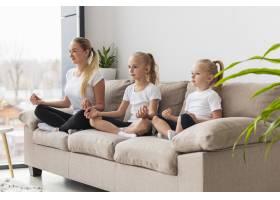 母女坐在家里沙发上冥想的侧观_7435908