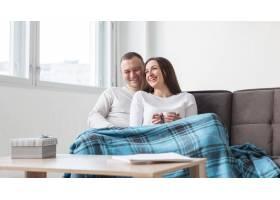 幸福的父母在沙发上放松_7089434