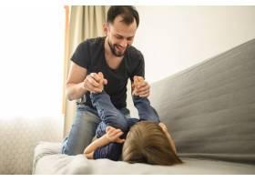 微笑的父亲和儿子在沙发上玩耍_7553277