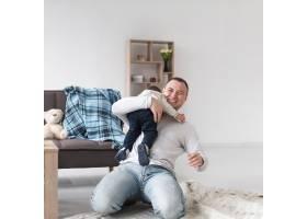 微笑的父亲在家里抱着孩子_7089372