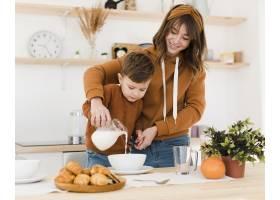 微笑的妈妈和儿子在厨房里_6881414