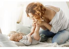 快乐的母亲和新生儿玩耍亲吻小腿在舒适_8811574