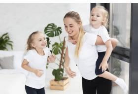 快乐的母亲在家里和微笑的女儿们在一起_7435952