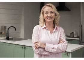 快乐的母亲微笑摆姿势在厨房里_6609144