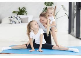 快乐的母女们在家中瑜伽席上_7435893