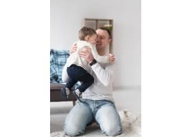 快乐的父亲在家里抱着孩子_7089309