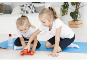 家中女孩坐在瑜伽垫上举重的前景_7435949