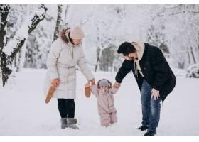 帶著小女兒的年輕家庭在滿是白雪的冬日森林_6641623