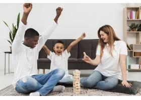 一个小男孩和他的父母在室内玩游戏_7132042