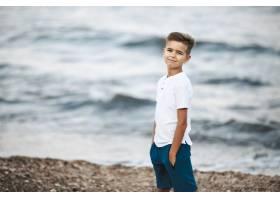 一个白人小男孩穿着白色t恤和蓝色短裤站在_7250328