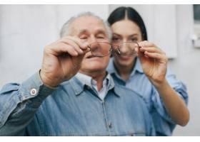 一位老人和他的孙女站在灰色的背景上_7590283