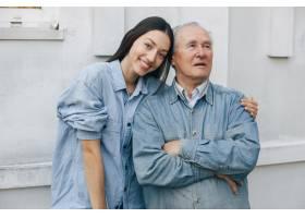 一位老人和他的孙女站在灰色的背景上_7590285
