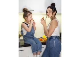 可爱的小女孩和妈妈一起吃橙子_7146638