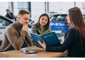 一对年轻夫妇在汽车展厅与销售人员交谈_7200774