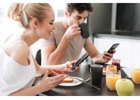 相当专注的情侣在厨房吃早餐时使用他们的智_6819635
