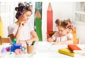 这位年轻的母亲和她的小女儿在家里用铅笔作_7570513