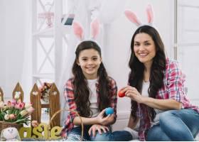 母女俩坐在一起手里拿着红蓝相间的复活节_3978626