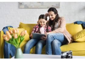 母女俩坐在黄色沙发上俯瞰_7063497