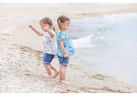 海边的孩子们沿着海水走的双胞胎_7570606
