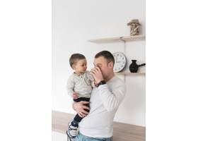 父亲一边抱着孩子一边喝着杯子里的水_7089302