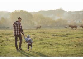 父亲带着年幼的儿子走在早晨的田野上_7169697