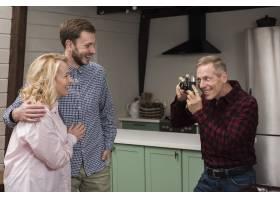微笑的爸爸在厨房里给妈妈和儿子拍照_6609158