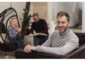微笑的男人和分散的父母在沙发上摆姿势_6608892