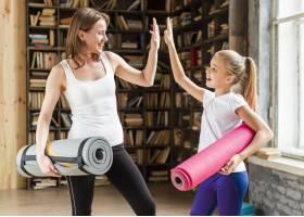 快乐的妈妈和女孩拿着瑜伽垫和击掌_7334130