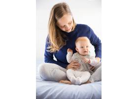 快乐的年轻新妈妈抱着她可爱的小宝宝_7548593