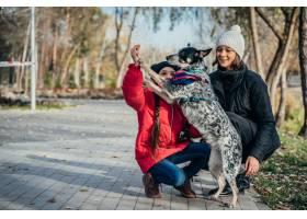 快乐的母亲和她的女儿在秋季公园玩狗_7283289