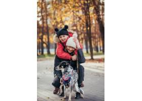 快乐的母亲和她的女儿在秋季公园玩狗_7283291