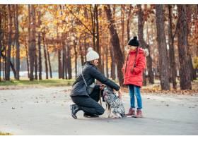 快乐的母亲和她的女儿在秋季公园玩狗_7408555