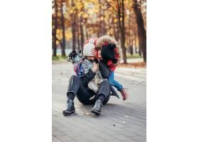 快乐的母亲和她的女儿在秋季公园玩狗_7408556