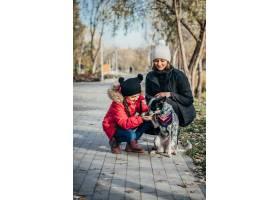 快乐的母亲和她的女儿在秋季公园玩狗_7560282