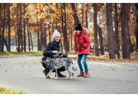 快乐的母亲和她的女儿在秋季公园玩狗_7560290