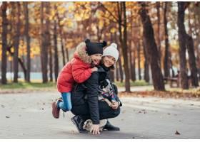 快乐的母亲和她的女儿在秋季公园玩狗_7560291