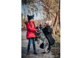 快乐的母亲和她的女儿在秋季公园遛狗_7408546