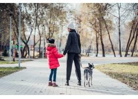 快乐的母亲和她的女儿在秋季公园遛狗_7408548