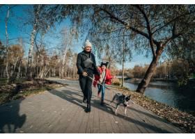 快乐的母亲和她的女儿在秋季公园遛狗_7560281