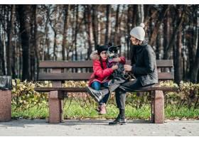 快乐的母亲和她的女儿带着狗在长凳上休息_7560283