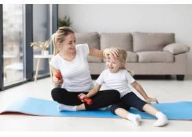 快乐的母亲带着女儿在家里的瑜伽垫上_7435923