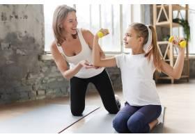 快乐的母亲帮助女儿在瑜伽垫上举重_7334095
