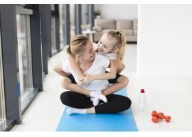 快乐的母子在瑜伽垫上举重的前景_7435756