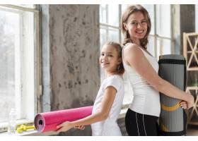拿着瑜伽垫的妈妈和女孩_7334128