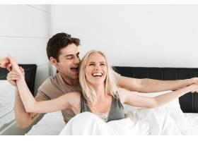 欢快有趣的恋人在床上拥抱大笑_6819615