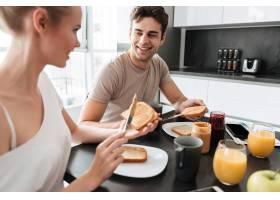 年轻漂亮的夫妇坐在厨房吃早餐_6819626