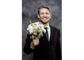 年轻帅气的新郎笑容满面手捧新娘花束_7591061