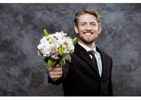 年轻帅气的新郎笑容满面手捧新娘花束_7591062